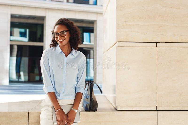 Uśmiechnięta bizneswoman pozycja na zewnątrz budynku biurowego obraz royalty free