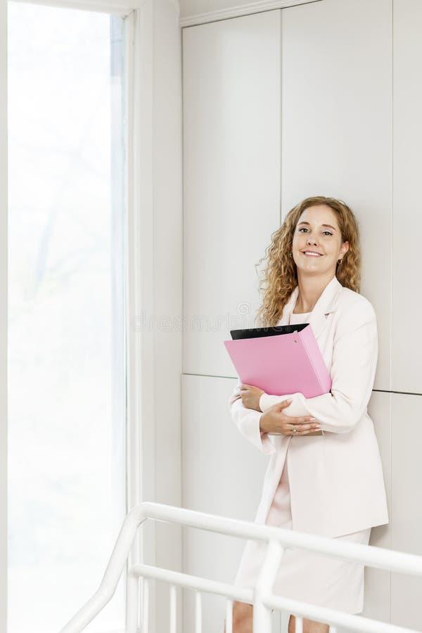 Uśmiechnięta bizneswoman pozycja w korytarzu obrazy royalty free