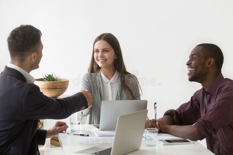 Uśmiechnięta bizneswomanu chwiania ręka męski partner przy grupowym spotkaniem zdjęcia royalty free
