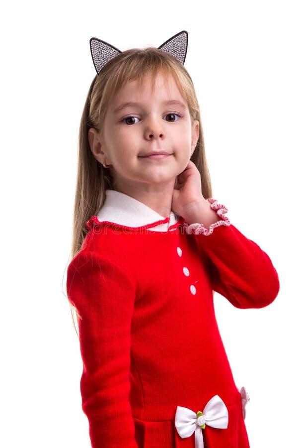 Uśmiechnięta blond dziewczyna w czerwonej sukni z kota ucho skrzyknie na białym odosobnionym tle, trzyma jej rękę za ucho fotografia stock