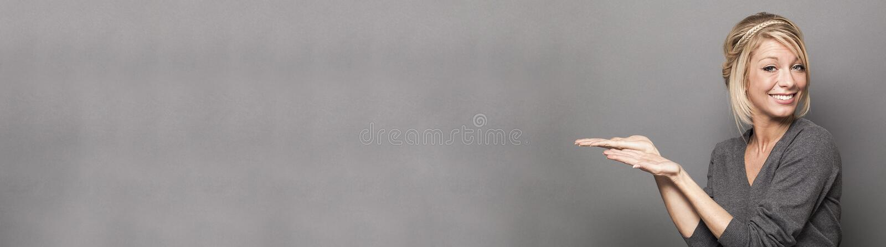 Uśmiechnięta blond kobieta pokazuje pustą lewej ręki strony przestrzeń fotografia royalty free