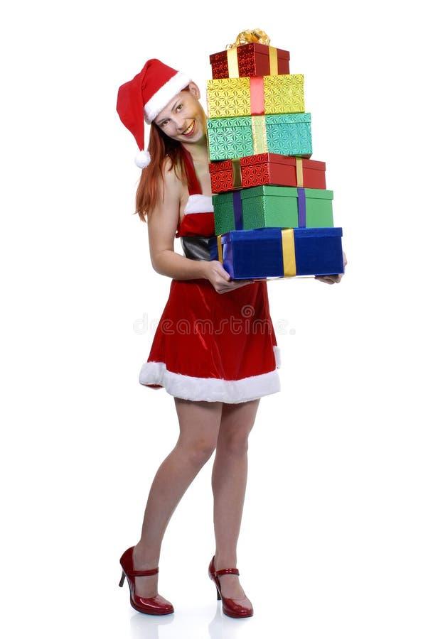 Uśmiechnięta Bożenarodzeniowa dziewczyna w Santa stroju z stosem prezenty odizolowywający na bielu, pionowo zdjęcia royalty free
