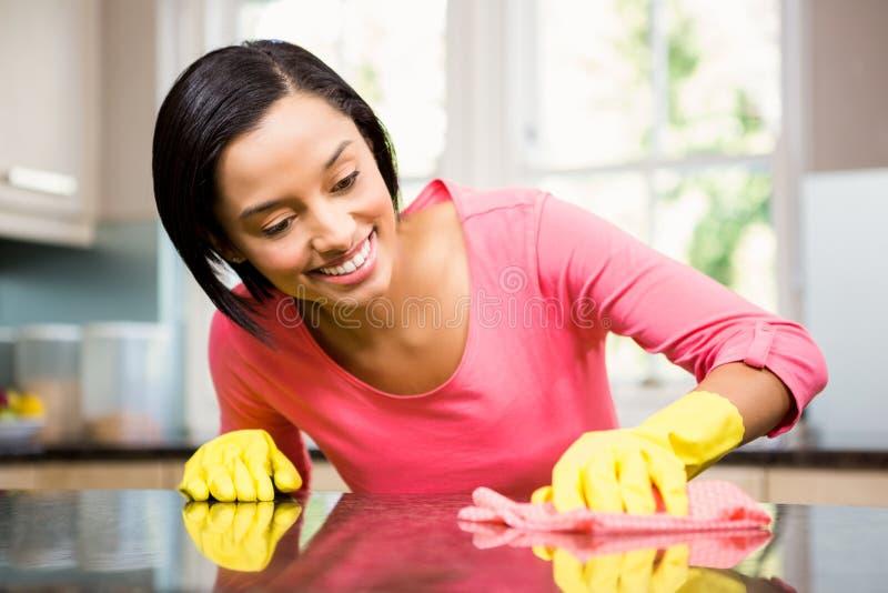 Uśmiechnięta brunetka czyści kuchennego kontuar obrazy stock