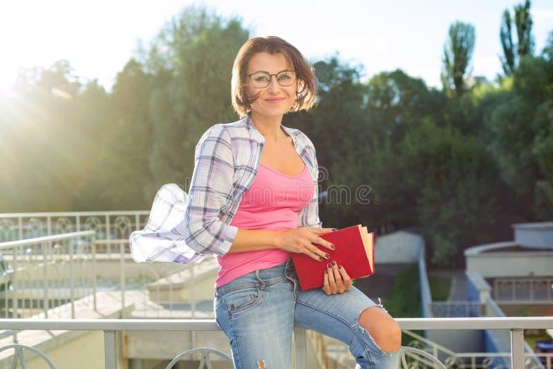 Uśmiechnięta brunetka relaksuje outdoors i czytelnicza książka zdjęcia royalty free