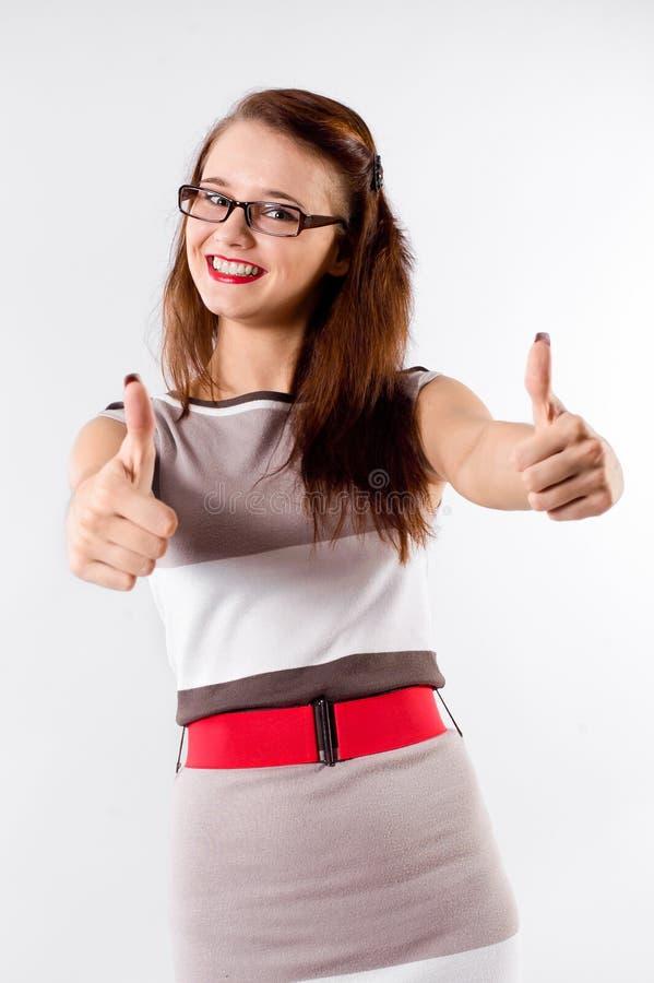Uśmiechnięta brunetki kobieta sygnalizuje ok w szkłach obraz stock