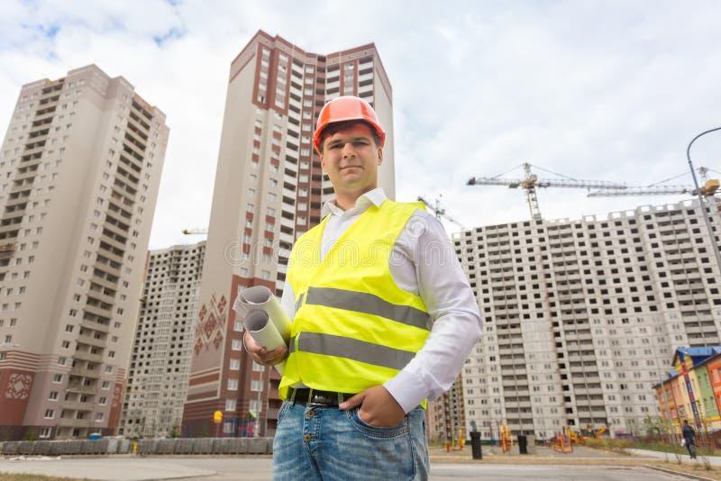 Uśmiechnięta budowa inżyniera pozycja przy placem budowy i chwytem obraz stock