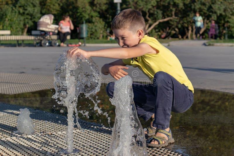 Uśmiechnięta caucasian chłopiec bawić się z fontanny wodą w miasto parku obraz royalty free