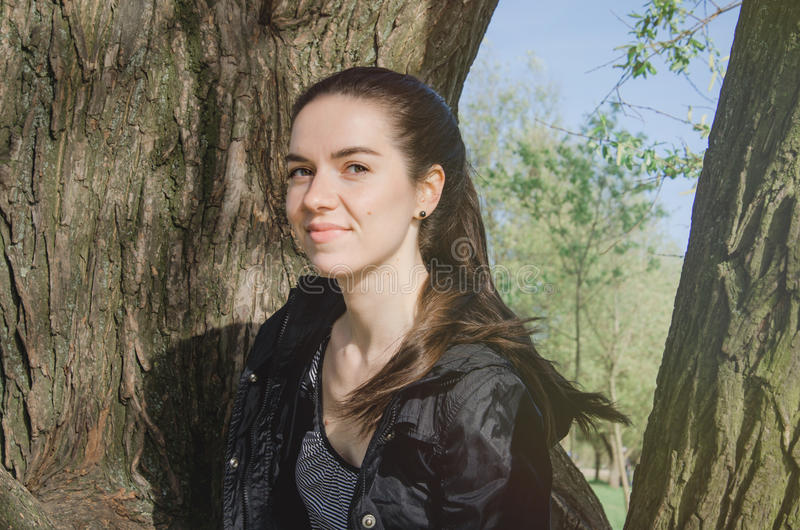 Uśmiechnięta caucasian młoda kobieta w czarnej kurtce na drzewnym natury tle, Plenerowy portret piękna brunetka fotografia stock
