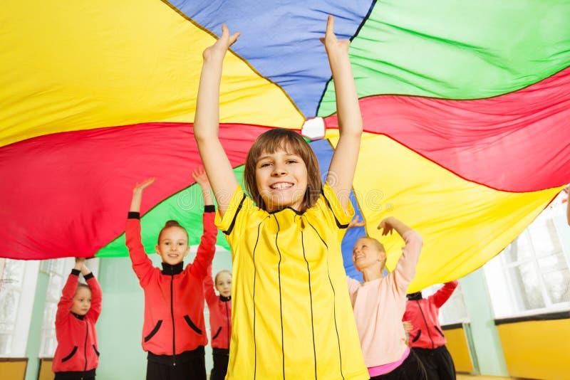 Uśmiechnięta chłopiec bawić się spadochronową grę obraz royalty free