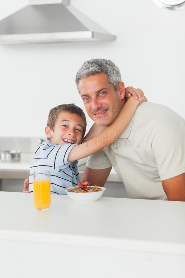 Uśmiechnięta chłopiec daje uściśnięciu jego ojciec podczas śniadania fotografia stock
