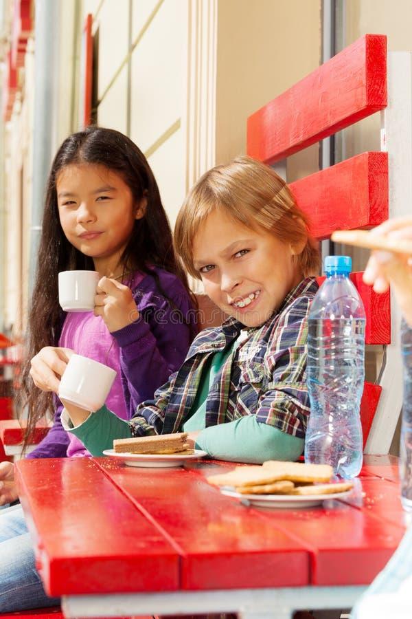 Uśmiechnięta chłopiec i śliczny dziewczyny obsiadanie w cukiernianym outside obraz stock