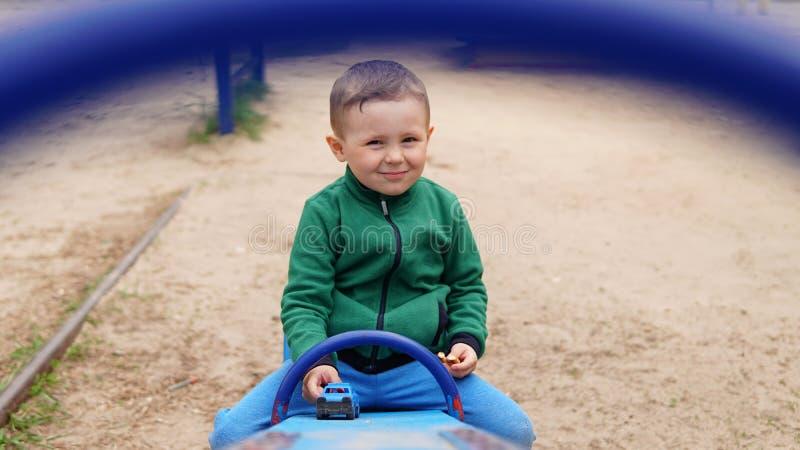 Uśmiechnięta chłopiec jazda na huśtawce i patrzeć kamerę w parku obraz stock