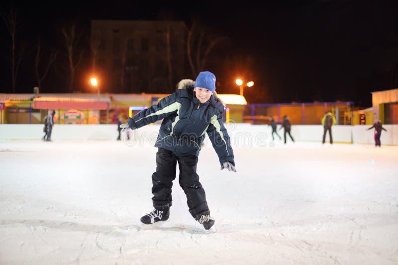Uśmiechnięta chłopiec jest ubranym w czarnym kostiumu i błękitnych kapeluszowych łyżwach fotografia stock