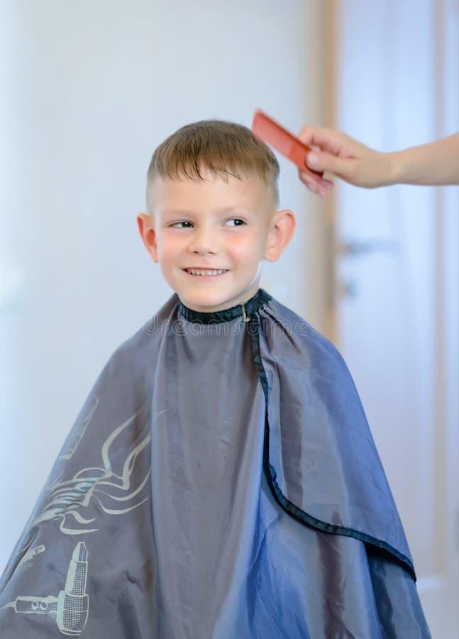 Uśmiechnięta chłopiec ma jego włosy ciącego obraz stock