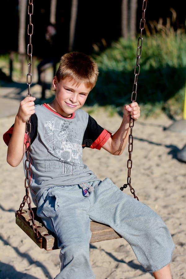 Uśmiechnięta chłopiec na huśtawce obrazy stock