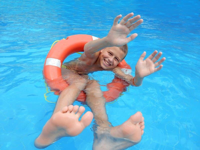 Uśmiechnięta chłopiec na lifebuoys obraz stock