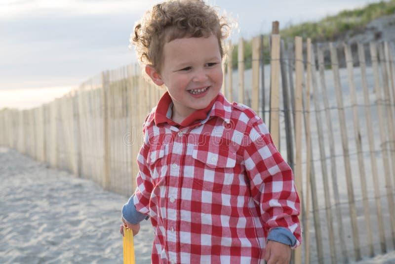 Uśmiechnięta chłopiec na plaży przed Drewnianym ogrodzeniem obrazy royalty free