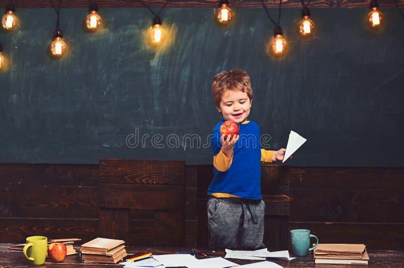 Uśmiechnięta chłopiec patrzeje smakowitego jabłka w jego ręce Blondynu dzieciaka mienia papieru samolot Szczęśliwa dziecko pozycj zdjęcia stock