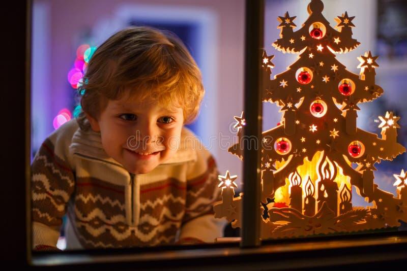 Uśmiechnięta chłopiec pozycja okno przy Bożenarodzeniowym czasem i mieniem może obrazy royalty free