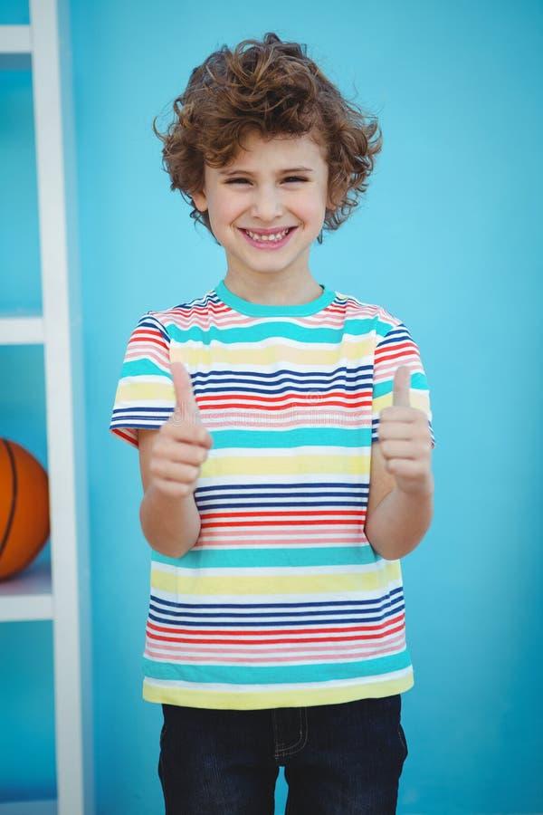 Uśmiechnięta chłopiec pozycja z aprobatami fotografia stock