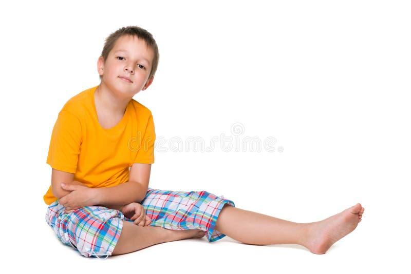 Uśmiechnięta chłopiec siedzi obrazy stock