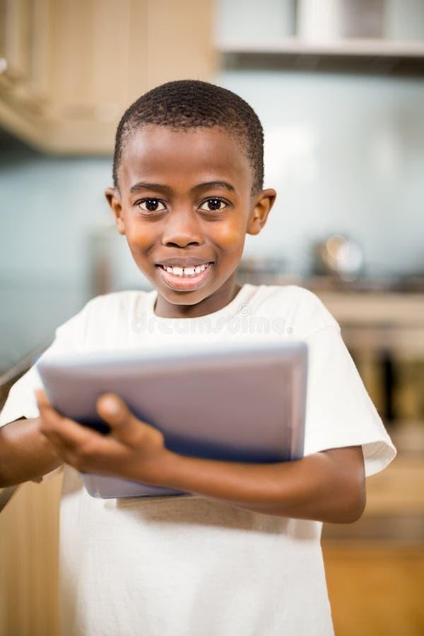 Uśmiechnięta chłopiec używa pastylkę fotografia royalty free