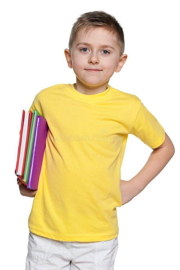 Uśmiechnięta chłopiec w żółtej koszula z książkami fotografia royalty free