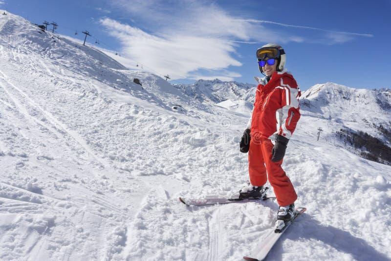 Uśmiechnięta chłopiec w narciarskim kostiumu na śniegu zdjęcia royalty free