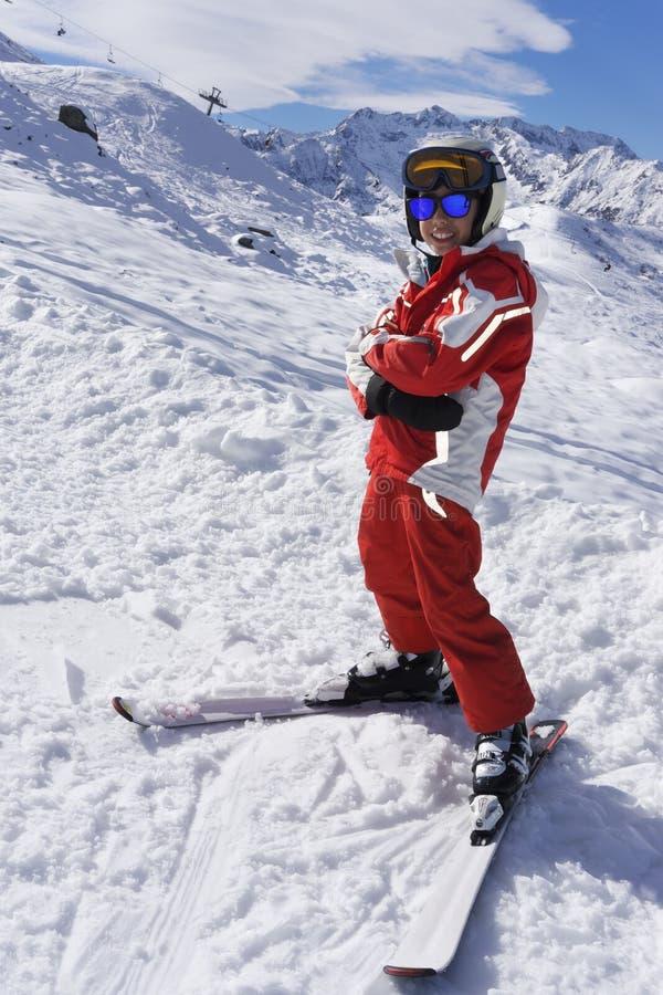 Uśmiechnięta chłopiec w narciarskim kostiumu na skłonie zdjęcia royalty free