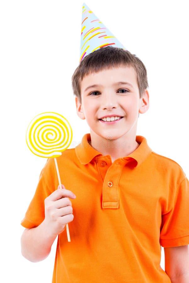 Uśmiechnięta chłopiec w partyjnym kapeluszu z barwionym cukierkiem zdjęcia royalty free