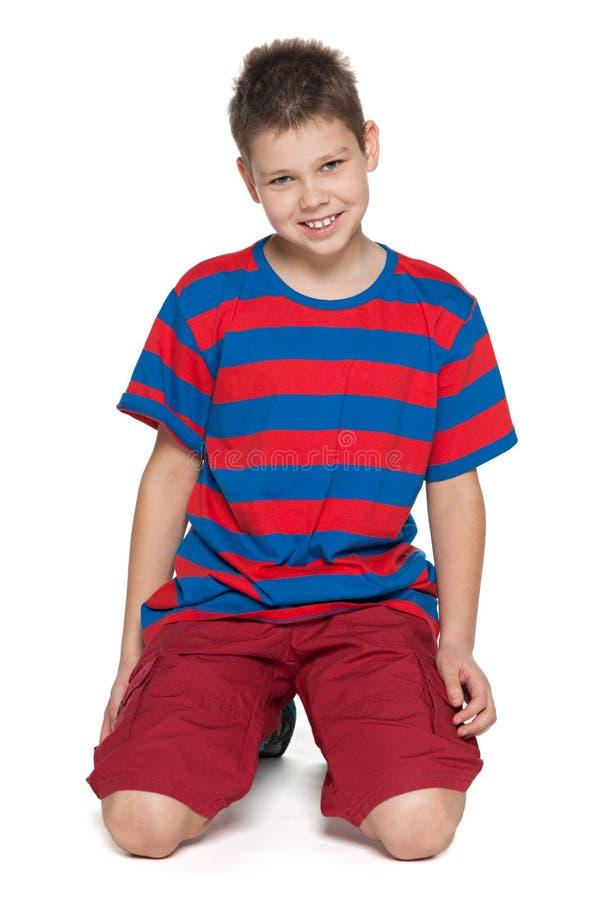 Uśmiechnięta chłopiec w pasiastej koszula na bielu zdjęcie stock