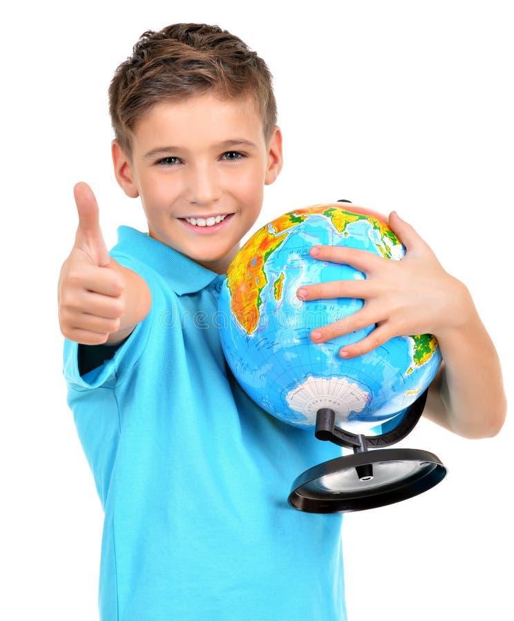 Uśmiechnięta chłopiec w przypadkowej mienie kuli ziemskiej z aprobatami obraz royalty free