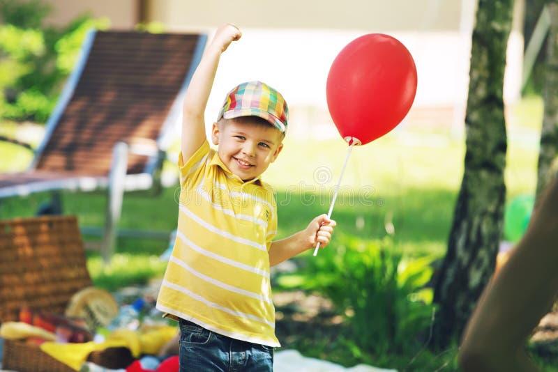 Uśmiechnięta chłopiec z czerwonym baloon fotografia stock