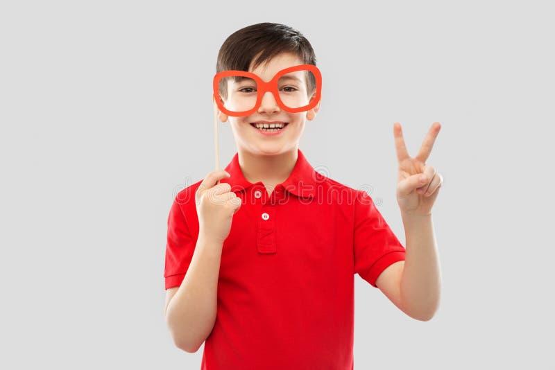 Uśmiechnięta chłopiec z dużymi papierowymi szkłami pokazuje pokój obraz stock