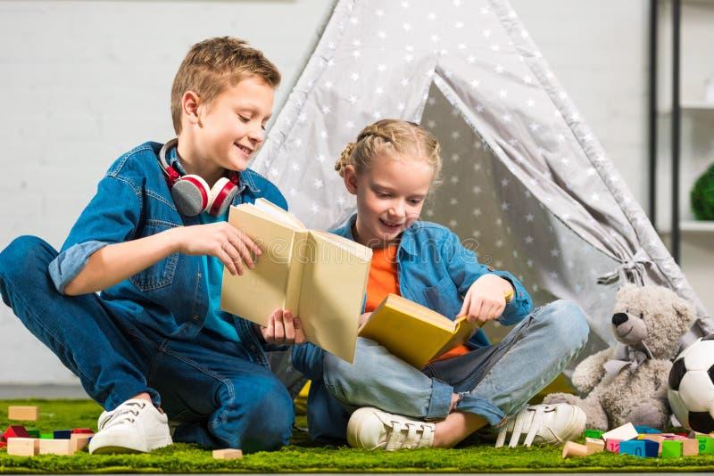 uśmiechnięta chłopiec z hełmofonami nad szyja seansu książką mała siostra blisko wigwamu zdjęcia stock