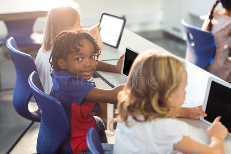 Uśmiechnięta chłopiec z kolega z klasy używa cyfrową pastylkę fotografia royalty free