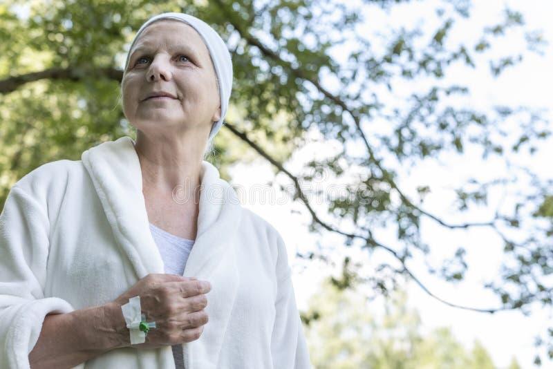 Uśmiechnięta chora starsza kobieta w opatrunkowej todze w lesie zdjęcie stock