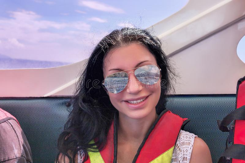 Uśmiechnięta ciemnowłosa kobieta żegluje na tropikalnym dennym jest ubranym lifejack obraz royalty free