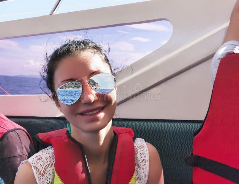 Uśmiechnięta ciemnowłosa kobieta żegluje na tropikalnym dennym jest ubranym lifejack obrazy royalty free