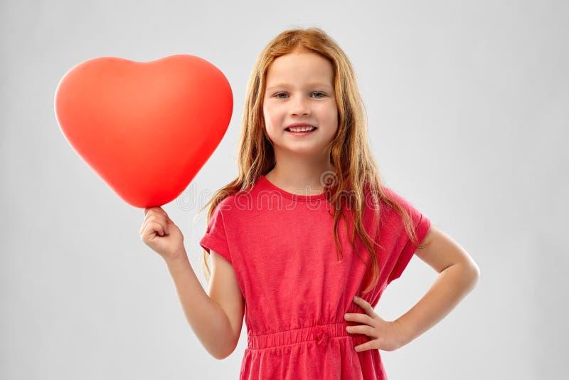 Uśmiechnięta czerwona z włosami dziewczyna z sercem kształtował balon obrazy royalty free