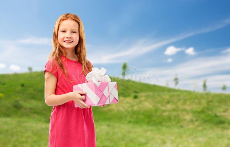 Uśmiechnięta czerwona z włosami dziewczyna z urodzinowym prezentem obraz stock