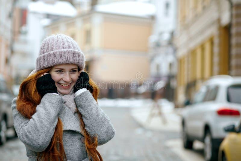 Uśmiechnięta czerwona z włosami kobieta jest ubranym ciepłej zimy odzieżowego odprowadzenie dow obraz stock