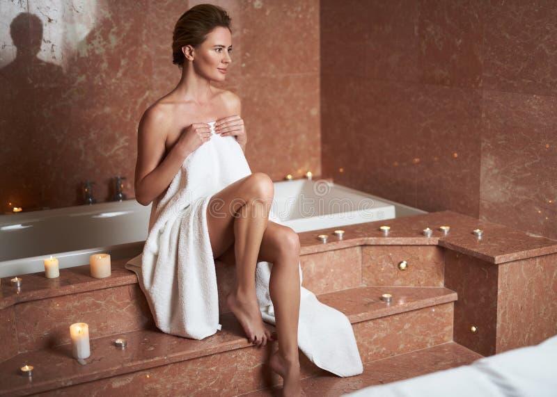Uśmiechnięta dama relaksuje w kąpielowym pokoju po zdroju fotografia stock