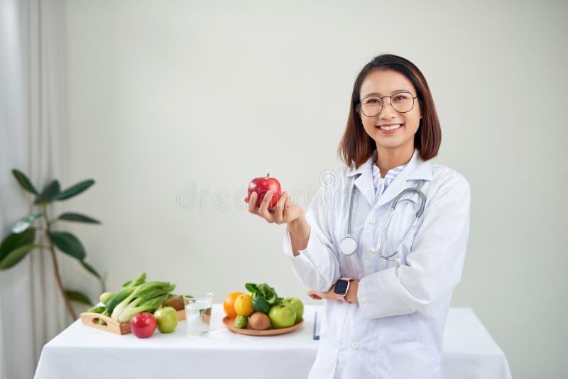 Uśmiechnięta dietetyka w swoim biurze, trzyma zielone jabłko i pokazuje zdrowe warzywa i owoce, opiekę zdrowotną i dietę zdjęcie royalty free