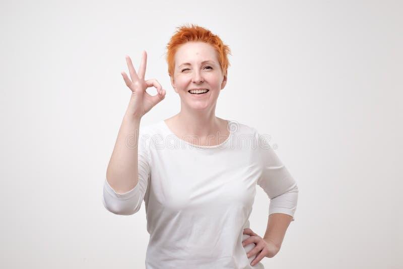 Uśmiechnięta dojrzała dama gestykuluje perfect znaka w białej koszulce obrazy royalty free