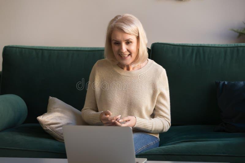 Uśmiechnięta dojrzała kobieta używa laptop, robi wideo wezwaniu w domu fotografia stock
