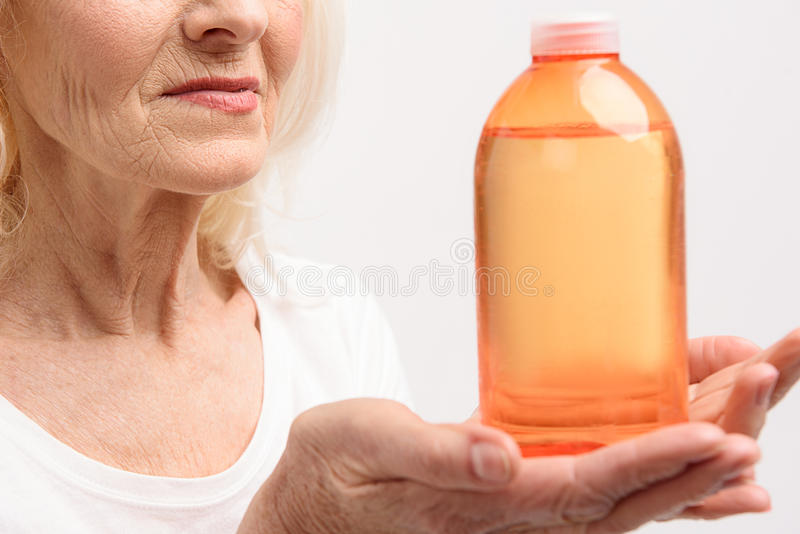 Uśmiechnięta dojrzała kobieta utrzymuje pomarańczową butelkę obraz stock