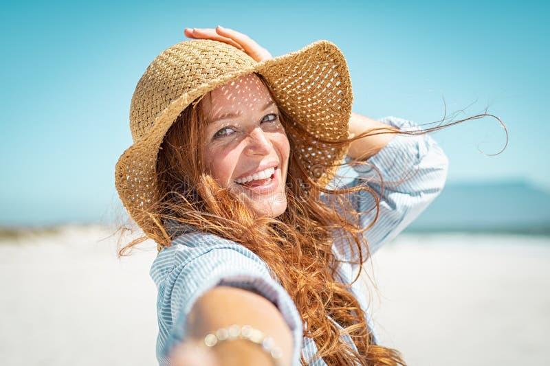 Uśmiechnięta dojrzała kobieta z słomianym kapeluszem zdjęcia royalty free