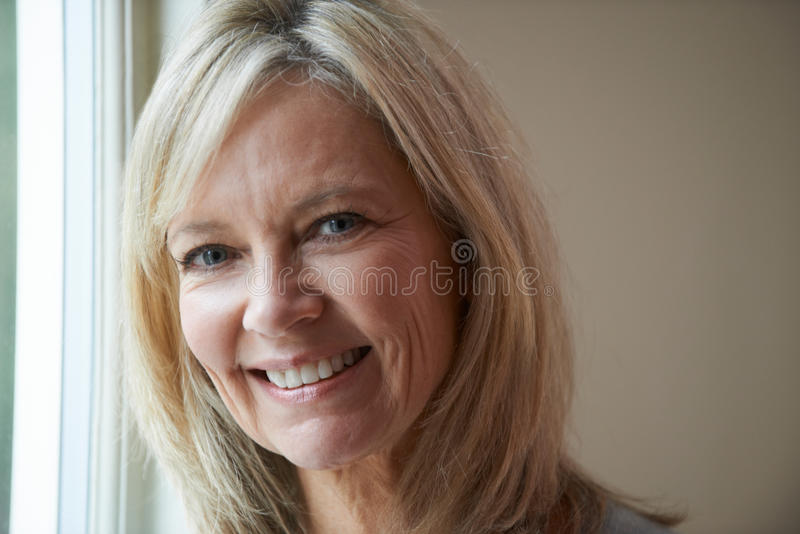 Uśmiechnięta Dojrzała kobiety pozycja Obok okno obraz royalty free