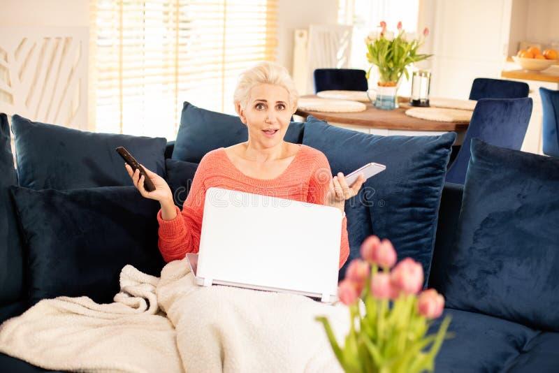 Uśmiechnięta dorosła dama relaksuje w domu z komputerem obraz royalty free